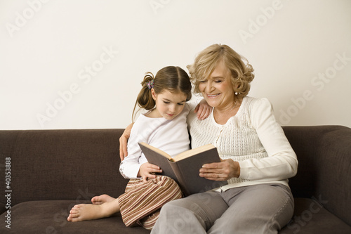 Senior woman with granddaughter reading book, smiling