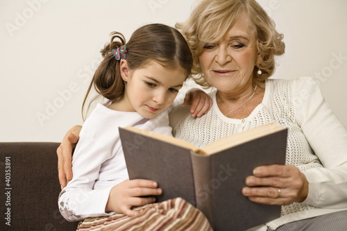 Senior woman with granddaughter reading book