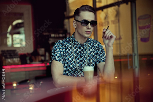 Handsome young man sitting in coffee bar