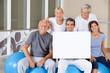 Senioren halten Schild im Fitnesscenter