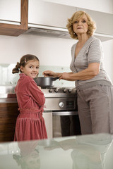 Senior woman with daughter in kitchen, portrait