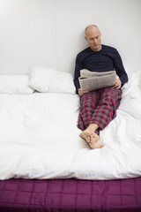 Mid adult man reading newspaper on bed