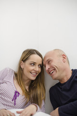 Mid adult couple leaning on wall, smiling