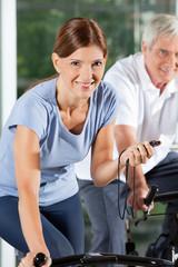 Lachende Frau mit Stoppuhr im Fitnesscenter