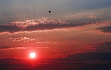 Lone paraglider over the red sunset.