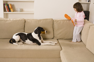Child playing with dog in living room