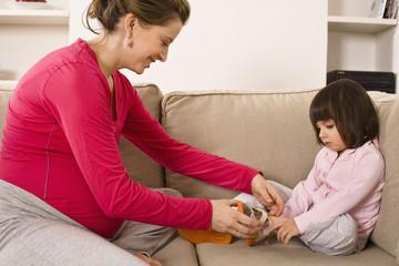 Woman adjusting daughter's shoe