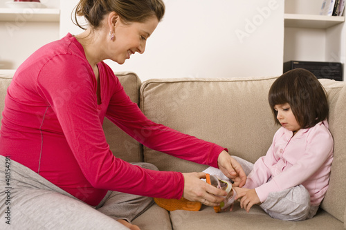 Woman adjusting daughter's shoe
