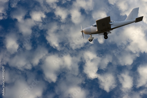 Clear blue sky with white clouds and white small airplane.