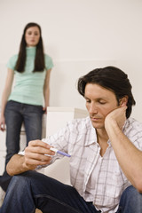 Man holding pregnancy test, woman standing in background