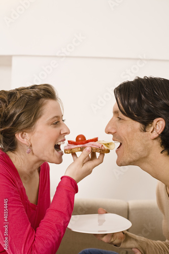 Man and woman sharing sandwich