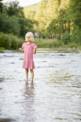 Girl standing in stream, portrait