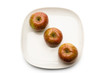 Three apples on plate, directly above