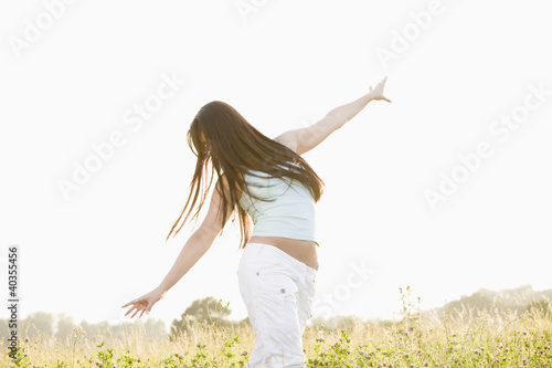 Young woman standing on field with arms outstretched