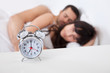 Lovely young couple and alarm clock