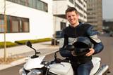 junger mit motorrad und helm