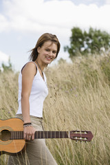 Mid adult woman holding guitar in field, portrait