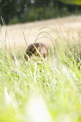 Mid adult woman sitting on field, portrait