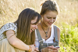 Mid adult women looking at mobile phone, smiling