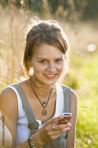 Mid adult woman holding mobile phone, smiling