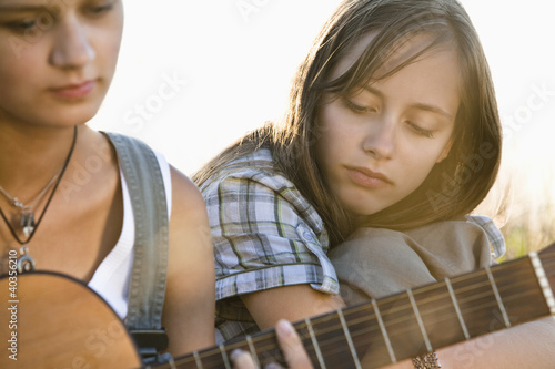Friends sitting on field with guitar, close-up