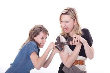 Zwei junge Frauen streiten sich um einen Schuh