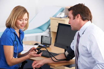 UK doctor taking patient's blood pressure