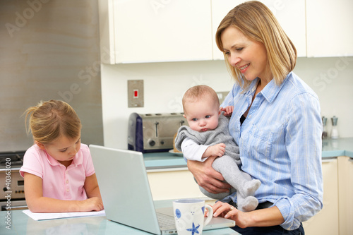Mother with children using laptop in kitchen