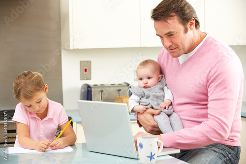 Father with children using laptop in kitchen