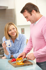 Mature couple preparing meal in domestic kitchen