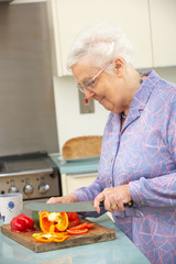 Senior woman chopping vegetables in domestic kitchen