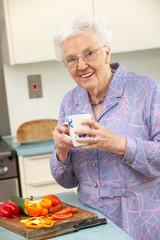 Senior woman preparing food in domestic kitchen