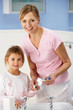 Mother and daughter cleaning teeth in bathroom
