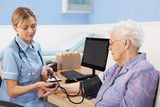 UK nurse taking senior woman's blood pressure