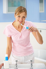 Woman cleaning teeth in bathroom