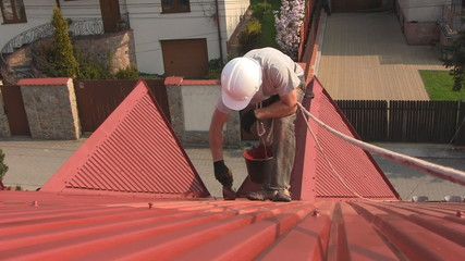 Painting roof of a private house with safety rope
