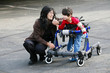 Mother with disabled son walking outdoors with walker