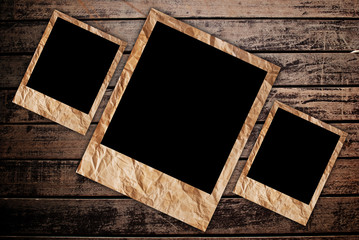 Vintage photo frame on the wood texture background.