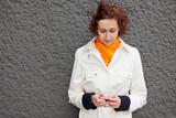 Frau mit Smartphone an Mauer