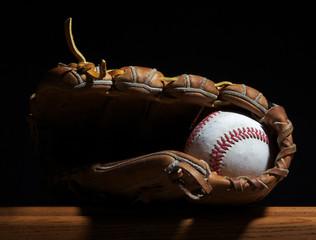 Baseball and mitt on a bench.