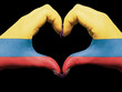 Heart and love gesture by hands colored in colombia flag for tou
