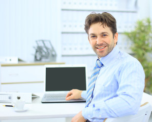Business man sitting at his desk in the office with a