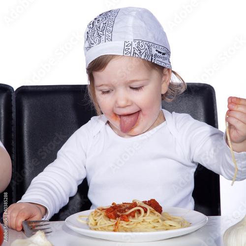 Kind isst Spaghetti und kleckert