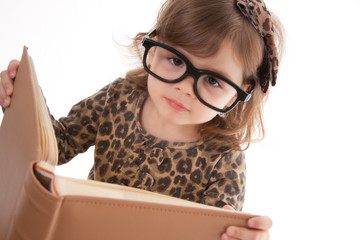 child reading a book, wearing large glasses
