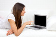 Woman lying on a sofa with laptop paying bills online