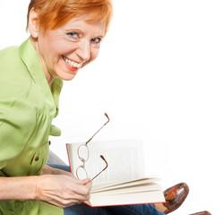 Reife Frau (64) liest ein Buch