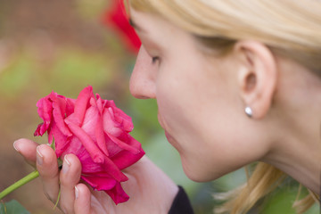 Lady  smelling a rose ih a baroque park