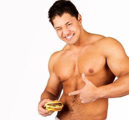 Young muscular man holding a hamburger