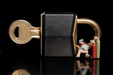 Miniatur arbeiter schweissen ein Schloss zu