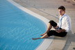 Young businessman working with feet in the pool